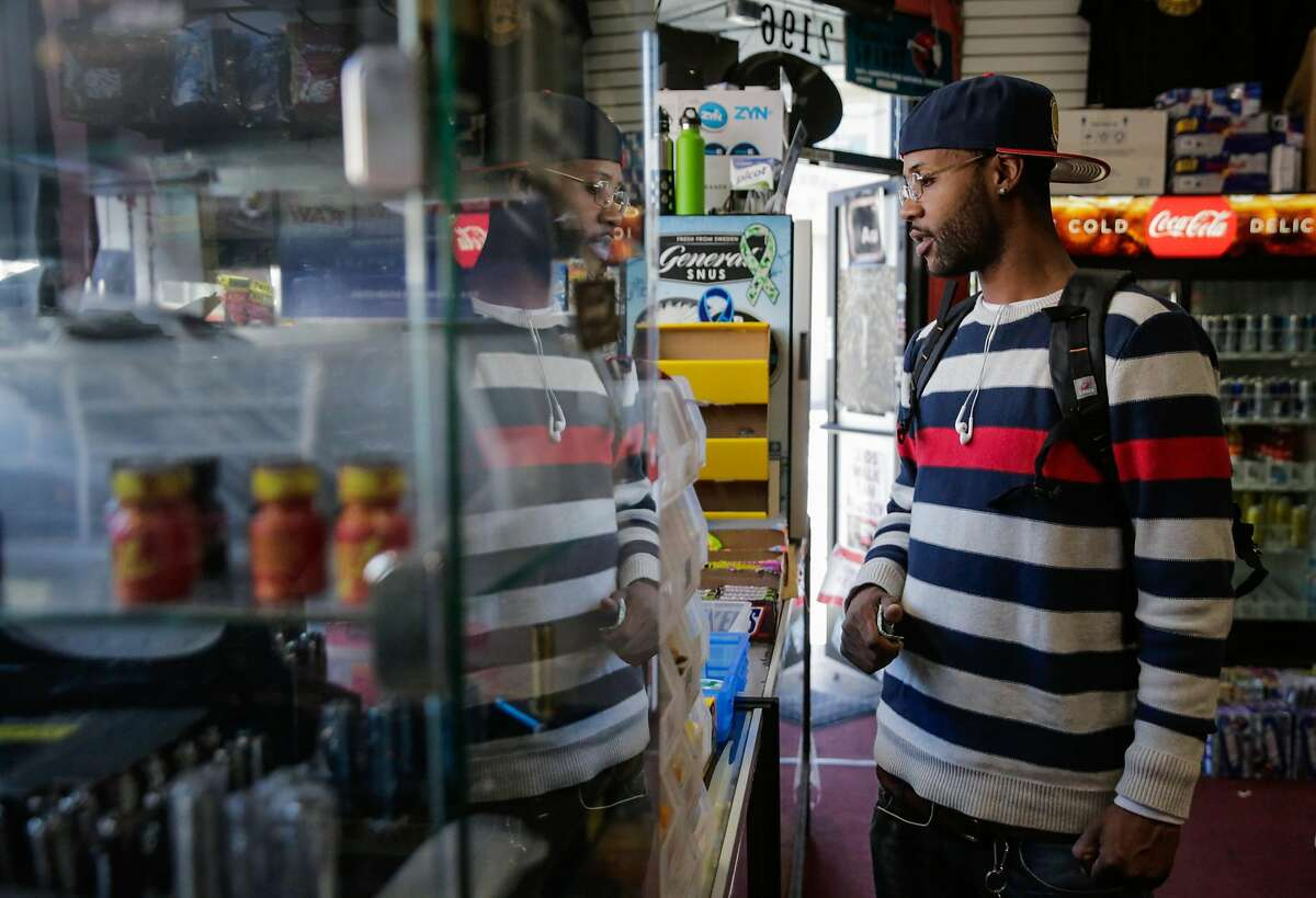 FILE - Keenan Jones looks at flavored tobacco as he shops at City Smoke and Vape Shop in San Francisco in this file photo from Sunday June 11, 2017. The Oakland City Council voted unanimously around midnight Wednesday to prohibit the sale of menthol cigarettes and flavored blunt wraps. The vote comes a month after San Francisco approved a similar ban.