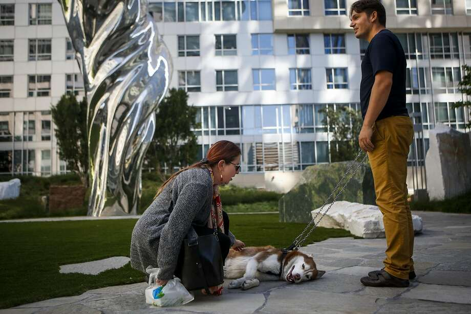 Patrice Vecchione, left, pets Ferran Arricivita's husky Ozzie, right, in front of artist Lawrence Argent's Venus de Milo statue in Trinity Place's Piazza Angelo courtyard in San Francisco on June 13, 2017. Photo: Nicole Boliaux, The Chronicle