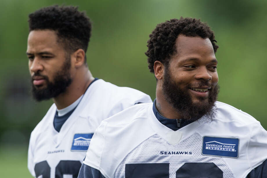 Defensive end Michael Bennett and free safety Earl Thomas wait for a drill to begin during Seahawks minicamp on Tuesday, June 13, 2017. Photo: GRANT HINDSLEY, SEATTLEPI.COM / SEATTLEPI.COM
