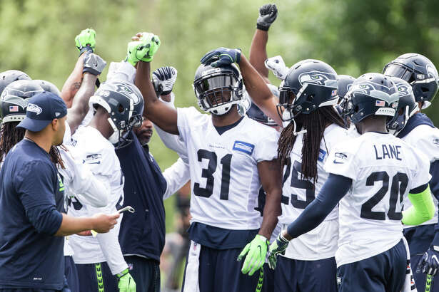 Defense huddles around cornerback Kam Chancellor during Seahawks minicamp on Tuesday, June 13, 2017.