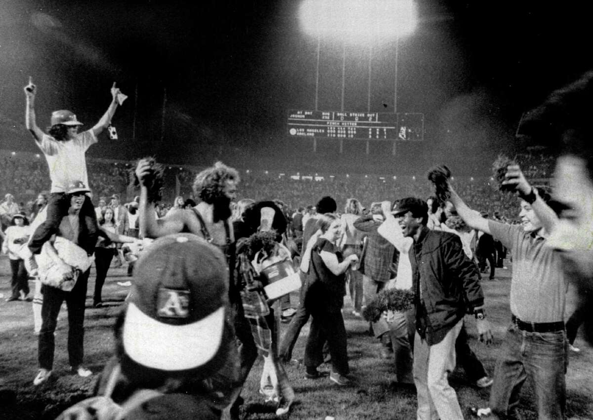 OAKLAND, CA - OCTOBER 17, 1974: Fans of the Oakland Athletics swarm the field and take souvenir samples of the turf home with them after the Athletics won 3-2 against the Los Angeles Dodgers in Game Five of the 1974 World Series on October 17, 1974 at Oakland-Alameda County Coliseum in Oakland, California. (Photo by Russ Reed/Sporting News via Getty Images)