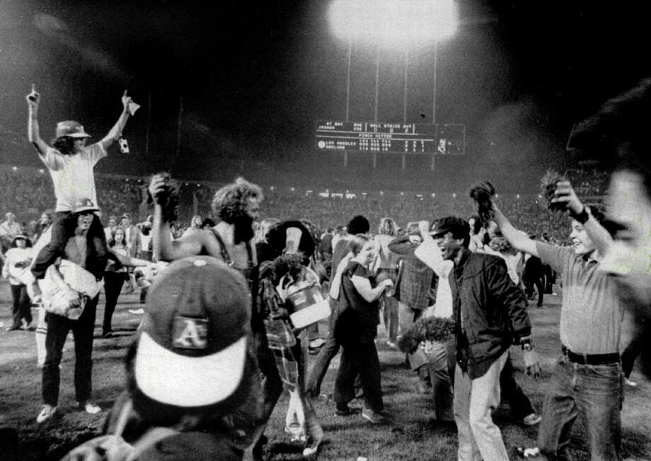 OAKLAND, CA - OCTOBER 17, 1974:  Fans of the Oakland Athletics swarm the field and take souvenir samples of the turf home with them after the Athletics won 3-2 against the Los Angeles Dodgers in Game Five of the 1974 World Series on October 17, 1974 at Oakland-Alameda County Coliseum in Oakland, California. (Photo by Russ Reed/Sporting News via Getty Images) Photo: The Sporting News / Sporting News Via Getty Images / 1974 Sporting News