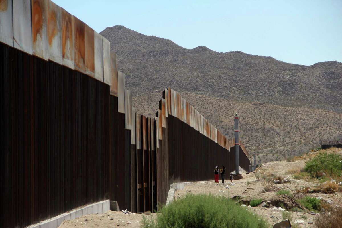 A Mexican family stands next to the border wall between Mexico and the United States in Ciudad Juarez, Mexico. (Herika Martinez/AFP/Getty Images)