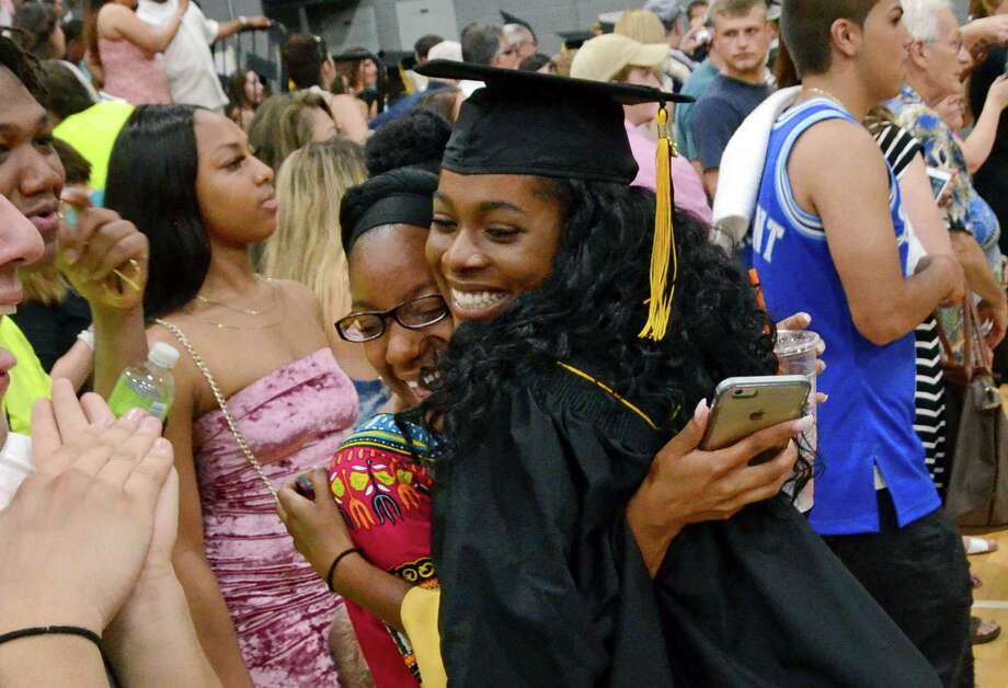 Graduate Kiara Smith hugs her friend Jaelyn Cooley, left, at the conclusion of Jonathan Law High School's 2017 graduation in Milford, Conn., on Tuesday June 13, 2017. Photo: Christian Abraham, Hearst Connecticut Media / Connecticut Post