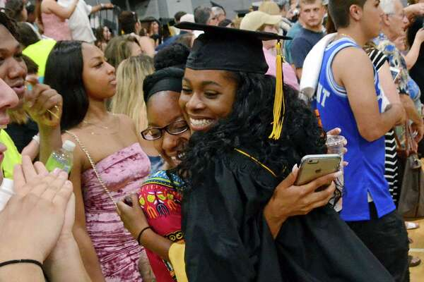 Graduate Kiara Smith hugs her friend Jaelyn Cooley, left, at the conclusion of Jonathan Law High School's 2017 graduation in Milford, Conn., on Tuesday June 13, 2017.