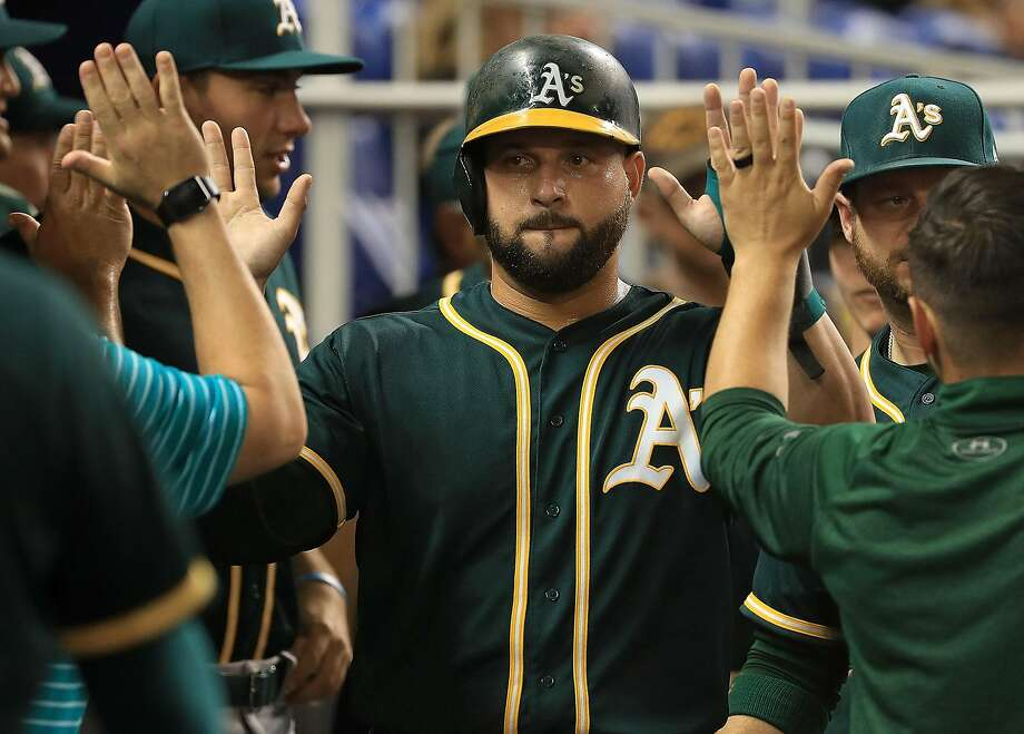MIAMI, FL - JUNE 13:  Yonder Alonso #17 of the Oakland Athletics is congratulated after scoring on a bases loaded balk in the second inning during a game against the Miami Marlins at Marlins Park on June 13, 2017 in Miami, Florida.  (Photo by Mike Ehrmann/Getty Images) Photo: Mike Ehrmann, Getty Images