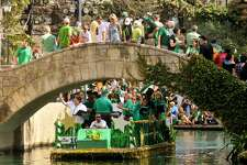 A parade barge passes under the Arneson Theater bridge on the dyed-green San Antonio River during the annual St. Patrick's Day Parade.