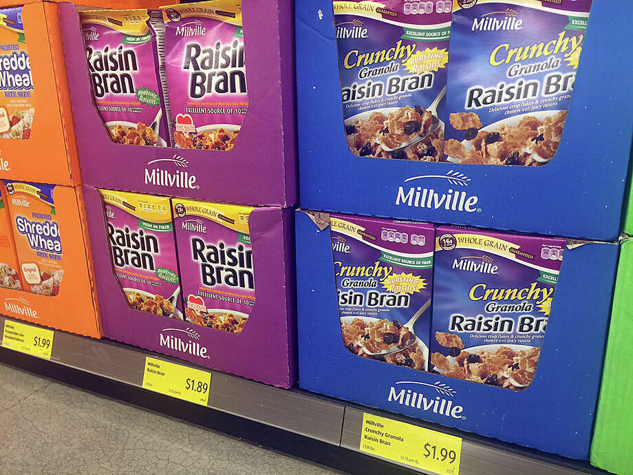 In this Saturday, May 20, 2017, photo, boxes of the Aldi food market chain's Millville Raisin Bran are on display in a purple box similar to the versions made by Kellogg and Post, at an Aldi store in New York. Stocking shelves with store brands is a big part of how discounters keep costs down. (AP Photo/Candice Choi) ORG XMIT: RPCC234 Photo: Candice Choi / AP