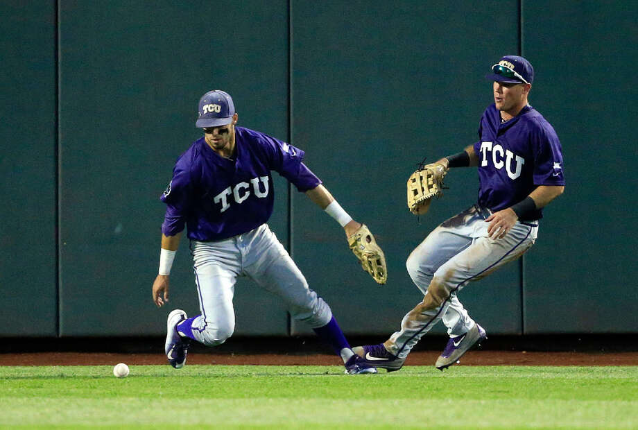 TCU center fielder Dane Steinhagen, left, and right fielder Austen Wade chase a ball hit by Coastal Carolina's G.K. Young during the fourth inning of an NCAA College World Series baseball game, Tuesday, June 21, 2016, in Omaha, Neb. (AP Photo/Nati Harnik)