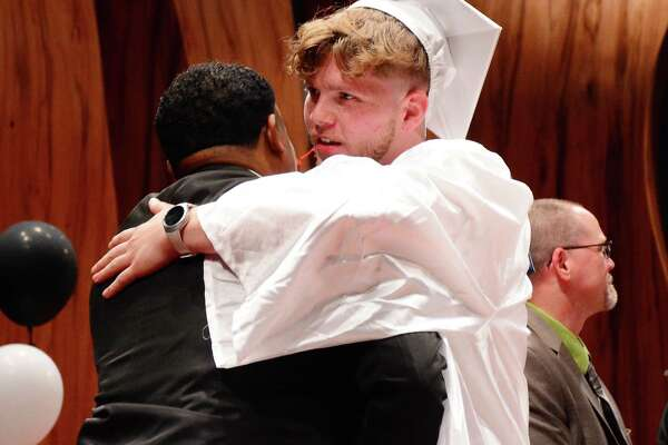 Toby Larsen gives the Regional Director of WERACE, Terence Cunningham, a hug has he recieves his diploma during their graduation ceremony that took place at Western Connecticut State University on Tuesday June 13, 2017.