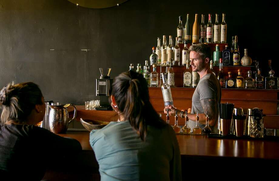 Bartender Decker McKerr shows a bottle of Tequila to two customers at Tequila Mockingbird. Photo: John Storey, Special To The Chronicle