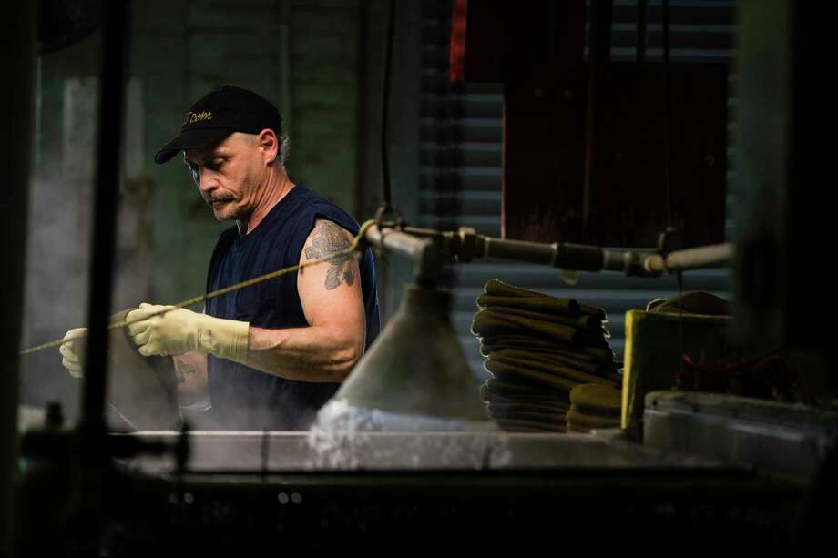 In this Monday, May 1, 2017, photo, a worker takes part in the manufacturing of hats the Bollman Hat Company in Adamstown, Pa. As another Fed rate hike nears, U.S. and global economies look healthier, but they still aren't as strong as they were a decade earlier. In the United States, factories have expanded nine straight months, bouncing back from a 2015-2016 slump caused by cutbacks in the energy industry and by a strong dollar that makes American-made products costlier overseas. (AP Photo/Matt Rourke) Photo: Matt Rourke, STF / Copyright 2017 The Associated Press. All rights reserved.