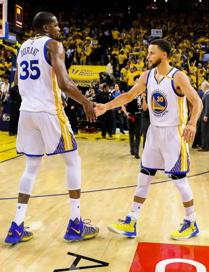 c6766367f473 Golden State Warriors player Kevin Durant (35) high-fives teammate Stephen  Curry (