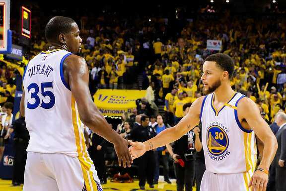 Golden State Warriors player Kevin Durant (35) high-fives teammate Stephen Curry (30) after winning Game 2 of the Western Conference Semifinals 2017 NBA playoffs between the Golden State Warriors and Utah Jazz at Oracle Arena in Oakland, California, on Thursday, May 4, 2017.