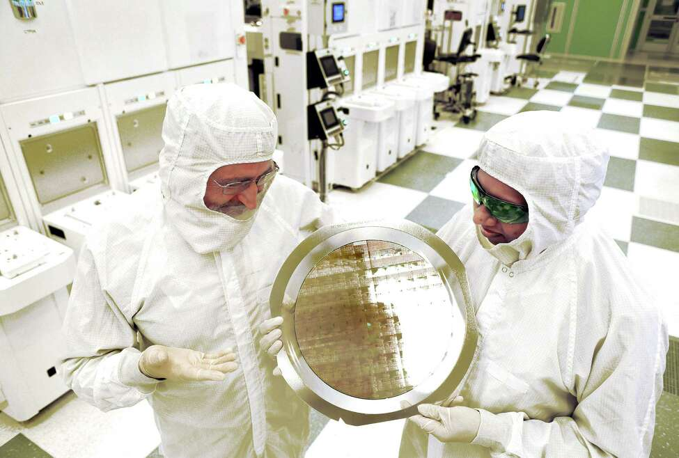 SUNY College of Nanoscale Science and Engineering's Michael Liehr, left, and IBM's Bala Haranand look at wafer comprised of 7nm chips on Thursday, July 2, 2015, in a NFX clean room at SUNY Polytechnic Institute Albany, N.Y. (Darryl Bautista/Feature Photo Service for IBM)