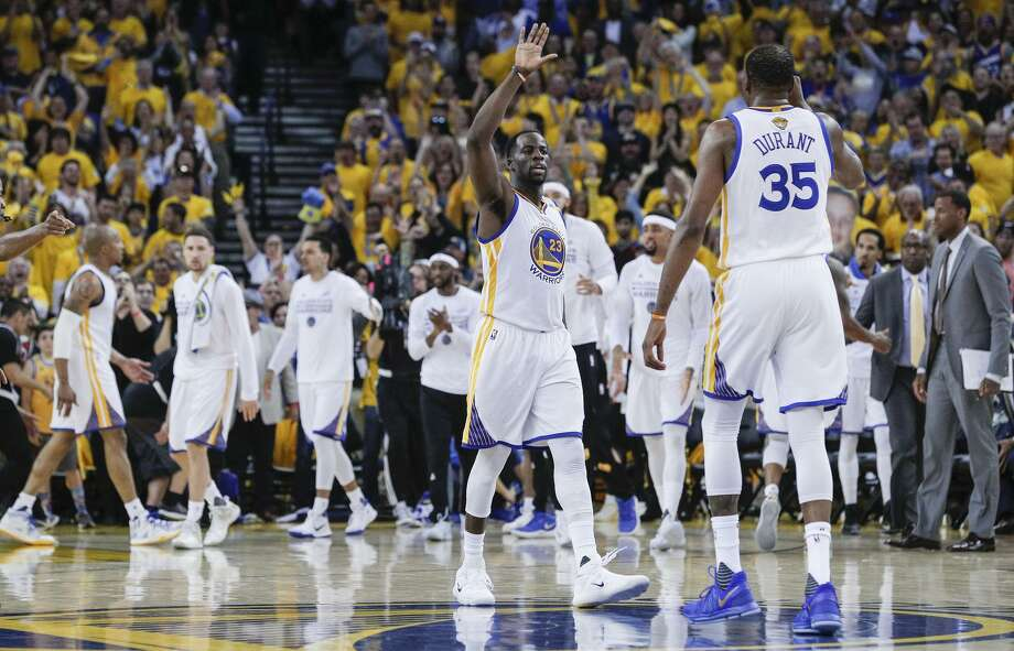 Draymond Green and Kevin Durant exchange a high-five in the second quarter of Game 5, when the Warriors seized control. Photo: Carlos Avila Gonzalez / The Chronicle / online_yes