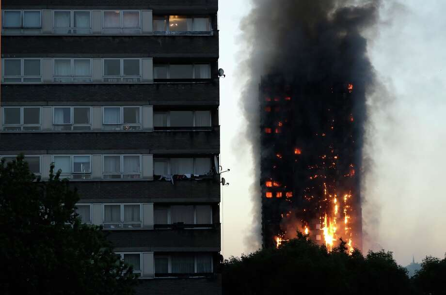 Smoke and flames rise from a building on fire in London, Wednesday, June 14, 2017. Metropolitan Police in London say they're continuing to evacuate people from a massive apartment fire in west London. The fire has been burning for more than three hours and stretches from the second to the 27th floor of the building.(AP Photo/Matt Dunham) Photo: Matt Dunham/AP