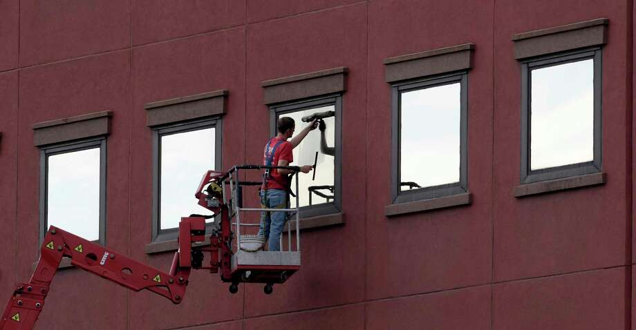 An Action Window Cleaning crew member takes a dry day to clean windows on a State Street office building Tuesday