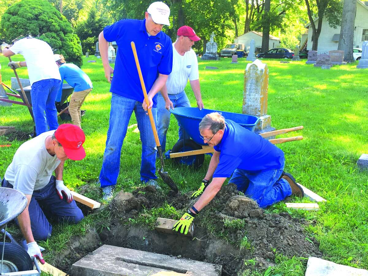 Knights of Columbus volunteers work to restore grave markers at St. Mary's Cemetery in Edwardsville.
