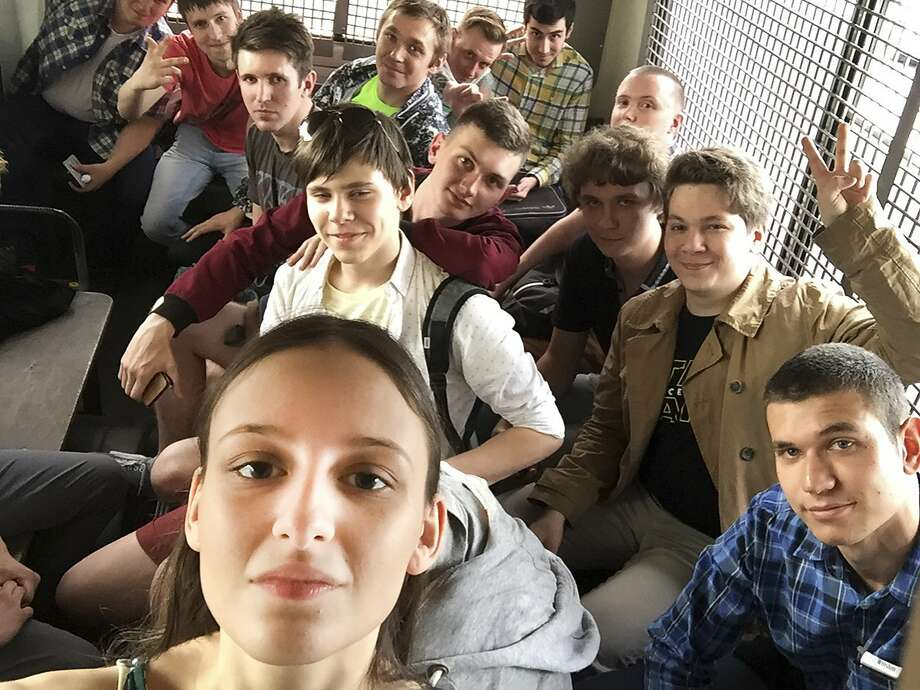 Young protesters sit inside a police bus after being detained during a rally in Moscow on Monday. Many students are demanding accountable government. Photo: Lyusya Shteyn, Associated Press