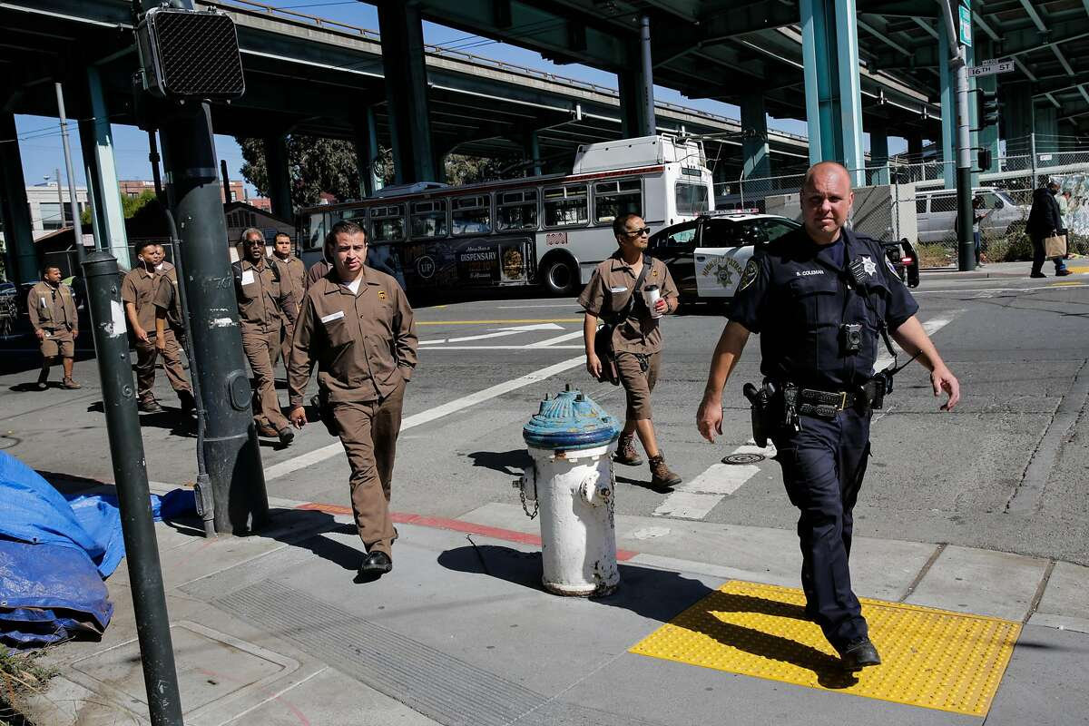 A police officer escorts UPS workers out of their building at the scene of an active shooting at 16th Street and Vermont Street in San Francisco, California, on Wednesday, June 14, 2017.