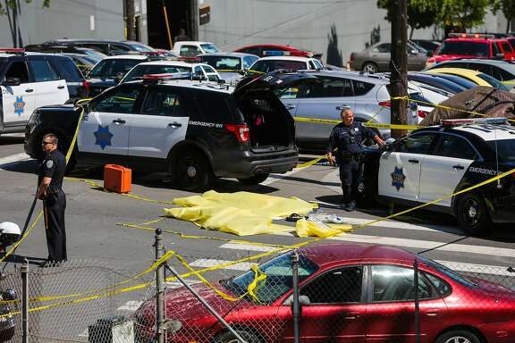 Police officers stand over a dead body at the scene of a fatal shooting at 17th Street and San Bruno Avenue in San Francisco, California, on Wednesday, June 14, 2017.
