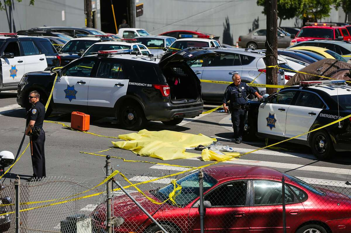 Police officers stand over a dead body at the scene of a fatal shooting at 17th Street and San Bruno Avenue in San Francisco on Wednesday, June 14, 2017.
