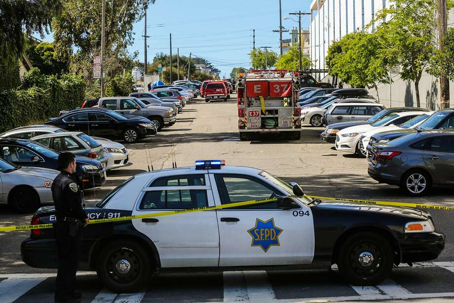 An officer helps guard the UPS building on San Bruno Avenue after a gunman went on a deadly rampage in June. Photo: Gabrielle Lurie, The Chronicle
