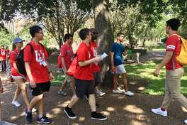 Daniel Tai, right, leads a group of incoming University of Houston students on a campus tour.