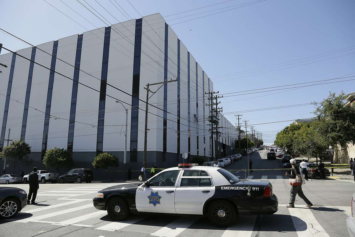 A San Francisco police car blocks a roadway outside a UPS package delivery warehouse where a shooting took place Wednesday, June 14, 2017, in San Francisco. A UPS spokesman says four people were injured in the shooting at the facility and that the shooter was an employee. (AP Photo/Eric Risberg)