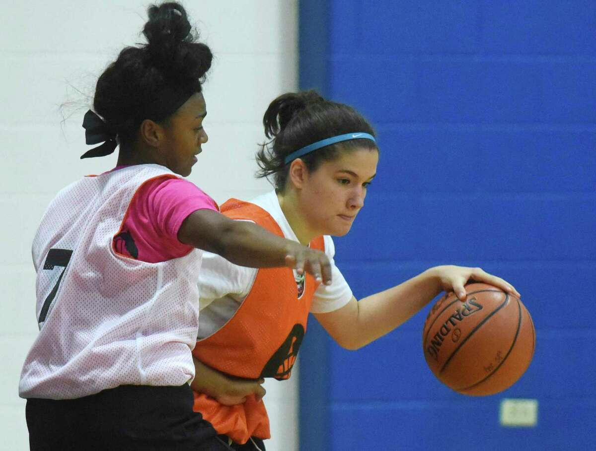 Ana Lacau (right), who has played basketball at Saint Mary's Hall, right, runs through a drill at Our Lady of the Lake University during the Basketball Embassy summer camp on Tuesday, June 13, 2017.