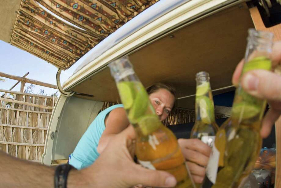 Three friends having a local Corona beer after reaching Loreto, the ending point of a roadtrip through Baja California, Mexico. ( Lars Schneider / Aurora Photos ) Photo: Lars Schneider, Contributor / Getty Images/Aurora Creative / This content is subject to copyright.