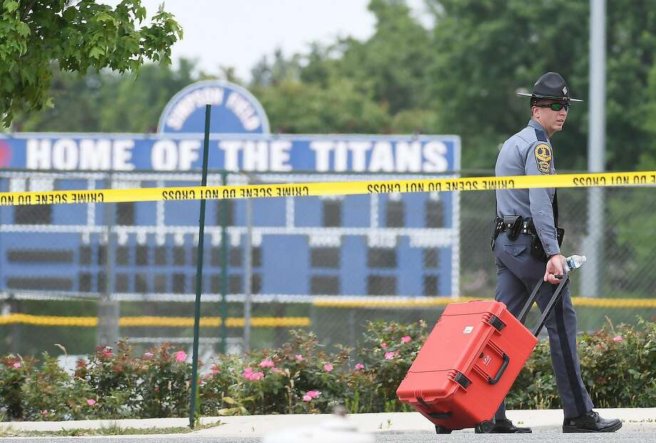 A police officer walks next to Eugene Simpson Stadium Park in Alexandria, Va., where the shooting took place as members of a Republican team practiced for a charity baseball team. Photo: Matt McClain, The Washington Post