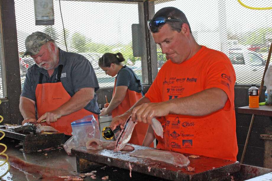 Volunteers clean some of the hundreds of fish caught for veterans to take home at a recent veteran's fishing outing. Photo: Rich Harp/For The Tribune