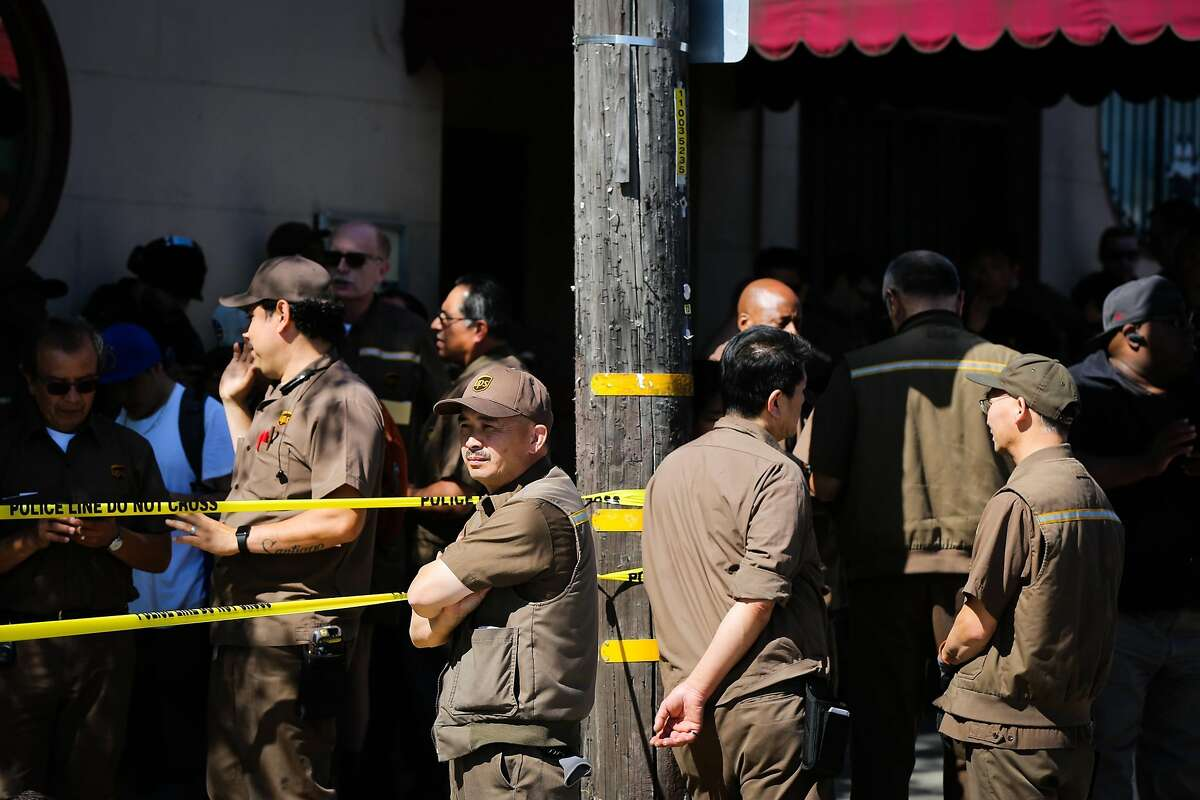 UPS workers who were evacuated from their building stand outside the scene of an active shooting on Utah Street and 16th Street in San Francisco, California, on Wednesday, June 14, 2017.