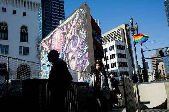 People come out of the BART station on Market Street between Van Ness Avenue and 12th Street in San Francisco, California, on Tuesday, June 13, 2017. The parking lot and building on the northwest corner of Van Ness Avenue will be the site of a new condo development.