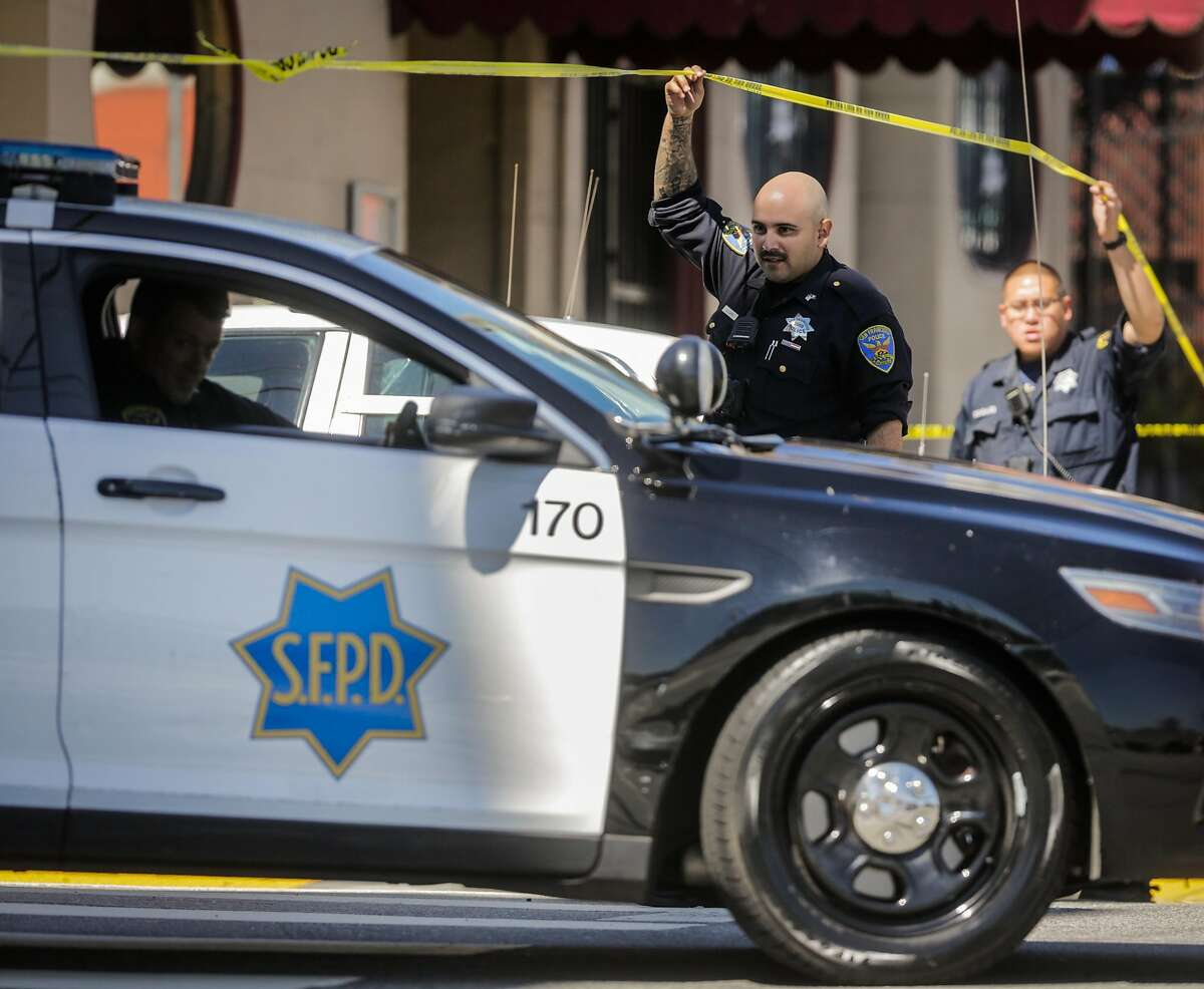 Police officers let a police car out of an active shooting crime scene on 16th Street and Utah Street in San Francisco, California, on Wednesday, June 14, 2017.