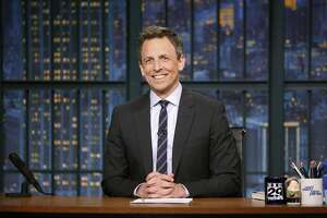"""This May 3, 2017 photo released by NBC shows Seth Meyers at his desk during a taping of, """"Late Night with Seth Meyers,"""" in New York. Meyers devotes up to 12 minutes of air time, three to four days a week, about the Trump Administration with a segment called A Closer Look. (Lloyd Bishop/NBC via AP)"""