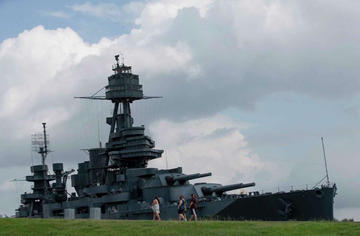 A group of people stop for a view of the 103-year-old Battleship Texas in La Porte. The battleship suffered leaks that caused it to tilt 8 degrees to one side. (Godofredo A. Vasquez / Houston Chronicle )