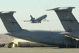 A KC-10 refueling tanker carrying 32 Port Mortuary Affairs specialists takes off between a pair of C-5's at Travis Air Force Base in Fairfield, Calif. Saturday, Sept. 15, 2001. The reservists volunteered to assist in the grim task of identifying and processing remains in the wake of the attacks on the United States. They were enroute to Dover AFB, Delaware. (AP Photo/Bob Galbraith)