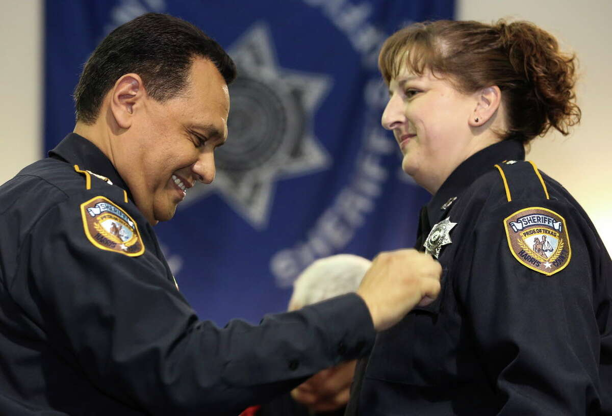 Harris County Sheriff Ed Gonzalez puts the new badge onto detention deputy Colleen Peake during a graduation ceremony Wednesday, June 14, 2017, at HCSO Training Academy in Humble.