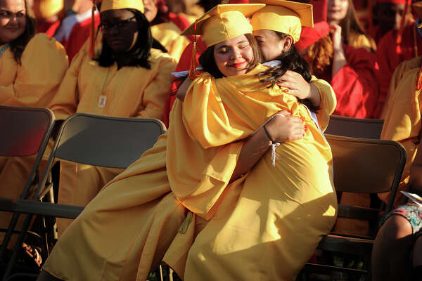 Friends Martha Polanco, left, and Angeleen Pingol share a hug during the Stratford High School graduation at Penders Field in Stratford, Conn on June 14, 2017.