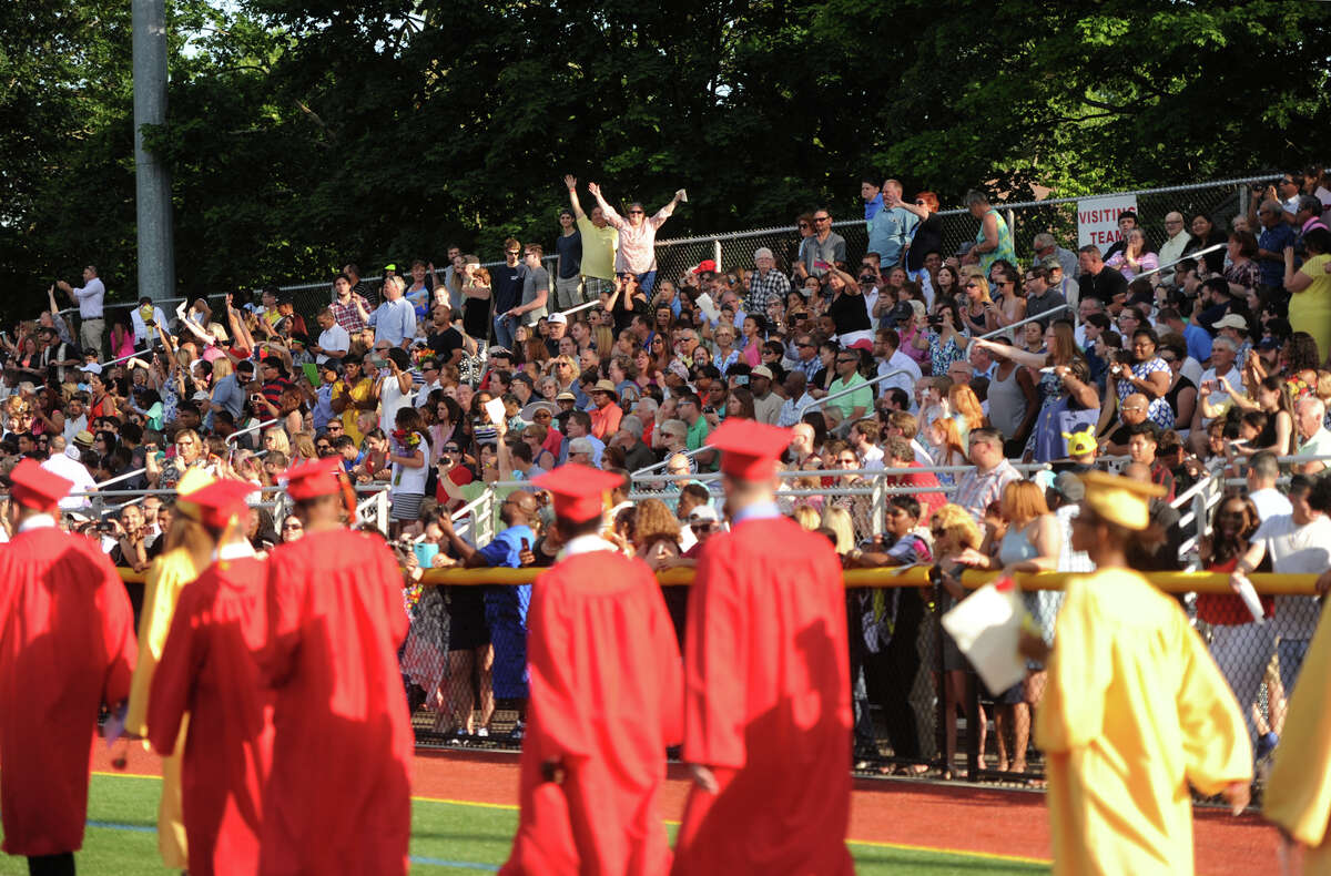 Families cheer on the graduates as they march in to the Stratford High School graduation at Penders Field in Stratford, Conn on June 14, 2017.