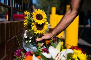 Jay Tanguay places flowers at the memorial set up in front of Creighton's Bakery & Cafe for Mike Lefiti, one of the victims of the UPS shooting in San Francisco, Calif. Wednesday, June 14, 2017. Tanguay is a resident of Diamond Heights and frequently saw Lefiti.