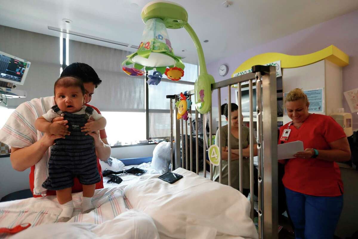 Emil Romero dresses his son Sebastian as they prepare to leave their hospital isolation room. Sebastian is responding well to a stem cell transplant three weeks ago.