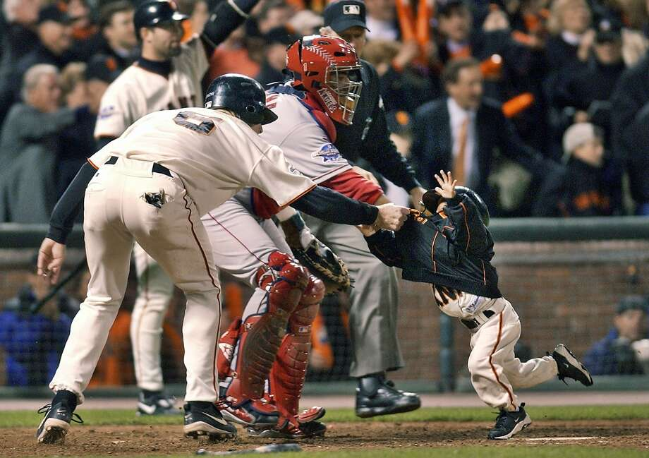 FILE - In this Oct. 24, 2002, file photo, San Francisco Giants' J.T. Snow, left, drags 3-year-old Darren Baker, son of then-Giants manager Dusty Baker, away from home plate and the path of oncoming baserunner David Bell, after Snow scored in the seventh inning of Game 5 of baseball's World Series in San Francisco. Darren Baker got scooped up by his father's team again. The son of Washington manager Dusty Baker was drafted by the Nationals in the 27th round of the Major League Baseball draft Wednesday, June 14--15 years after he first headlines on the baseball diamond. (AP Photo/Kevork Djansezian, File) Photo: Kevork Djansezian, Associated Press