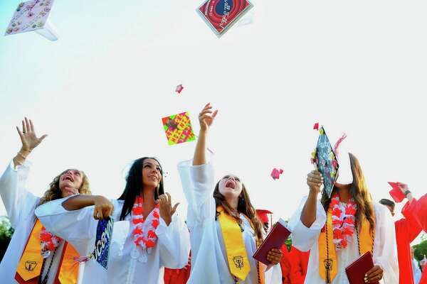 Graduate Anna Chevarella, center, tosses her cap in the air during Derby High School's 141st Commencement Ceremony in Derby, Conn., on Wednesday June 14, 2017.