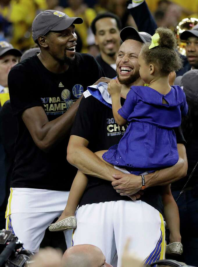 Golden State Warriors guard Stephen Curry, center, holds his daughter Riley as they celebrate with forward Kevin Durant, left, after Game 5 of basketball's NBA Finals against the Cleveland Cavaliers in Oakland, Calif., Monday, June 12, 2017. The Warriors won 129-120 to win the NBA championship. (AP Photo/Marcio Jose Sanchez) ORG XMIT: OAS178 Photo: Marcio Jose Sanchez / Copyright 2017 The Associated Press. All rights reserved.