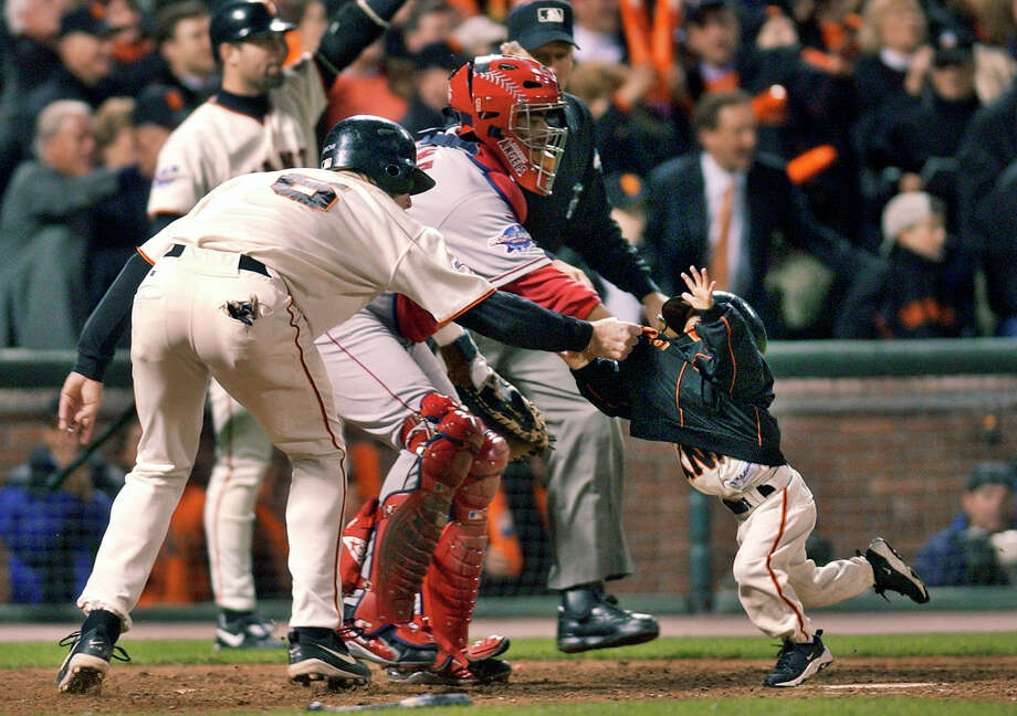 FILE - In this Oct. 24, 2002, file photo, San Francisco Giants' J.T. Snow, left, drags 3-year-old Darren Baker, son of then-Giants manager Dusty Baker, away from home plate and the path of oncoming baserunner David Bell, after Snow scored in the seventh inning of Game 5 of baseball's World Series in San Francisco. Darren Baker got scooped up by his father's team again. The son of Washington manager Dusty Baker was drafted by the Nationals in the 27th round of the Major League Baseball draft Wednesday, June 14--15 years after he first headlines on the baseball diamond. (AP Photo/Kevork Djansezian, File) ORG XMIT: NY169 Photo: Kevork Djansezian / Copyright 2017 The Associated Press. All rights reserved.