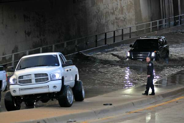 A Midland Police Department officer looks on as vehicles navigate the flood water near the Big Spring overpass after a storm on June 14, 2017.  James Durbin/Reporter-Telegram